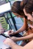 Couples de jeunes étudiants à l'aide d'un comprimé numérique dans la barre Image stock