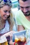 Couples de jeunes étudiants à l'aide d'un comprimé numérique dans la barre Photographie stock