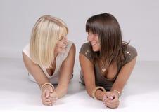 Couples de jeunes femmes de sourire se trouvant sur l'étage Image stock