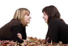 Couples de jeunes girlfiends se situant dans des lames d'automne Photos stock