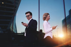 Couples de jeunes hommes d'affaires à l'aide des téléphones portables se tenant contre l'immeuble de bureaux avec la réflexion de Photographie stock libre de droits