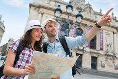Couples de jeunes touristes attirants observant la carte Photo stock