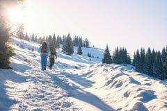 Couples de jeunes touristes trimardant en montagnes d'hiver Photo stock
