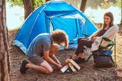 Couples de jeunes voyageurs passant le jour dans la for?t ensoleill?e pr?s de la tente photos stock