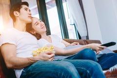 Couples de l'adolescence asiatiques regardant la TV ensemble Photos stock