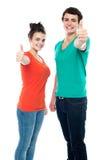 Couples de l'adolescence d'amour affichant des pouces jusqu'à l'appareil-photo Photo stock