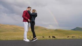 Couples de l'adolescence dans l'amour étreignant et embrassant tandis qu'ils prenant des photos de selfie avec l'arc-en-ciel et l banque de vidéos