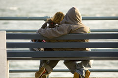 Couples de l'adolescence dans l'amour, banc Photos stock