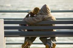 Couples de l'adolescence dans l'amour, banc Photos stock