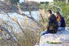 Couples de l'adolescence réfléchis d'âge parlant en parc Image stock
