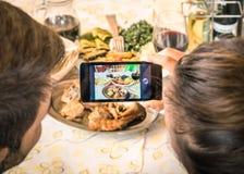 Couples de l'ami et de l'amie prenant un selfie de nourriture Image libre de droits