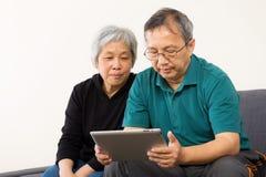 Couples de l'Asie utilisant le comprimé Images libres de droits