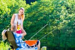 Couples de la femme et de l'homme ayant la bière tandis que pêche sportive Image libre de droits