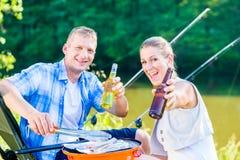 Couples de la femme et de l'homme ayant le BBQ après pêche sportive Photographie stock libre de droits