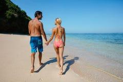 Couples de lune de miel tenant des mains marchant sur la plage Photographie stock