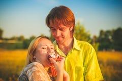 Couples de lune de miel romantiques dans l'amour au coucher du soleil de champ et d'arbres Couples heureux de nouveaux mariés jeu Photographie stock libre de droits