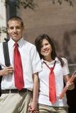 Couples de lycée dans l'uniforme tenant des mains Photo libre de droits