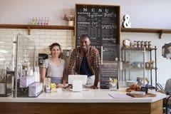 Couples de métis attendant derrière le compteur à un café image stock