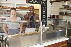 Couples de métis attendant derrière le compteur à une barre de sandwich images stock