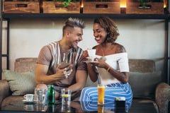 Couples de métis ayant l'amusement au café utilisant Photos libres de droits