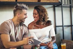 Couples de métis ayant l'amusement au café utilisant Photographie stock libre de droits