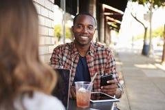 Couples de métis détendant à une table en dehors d'un café photos stock