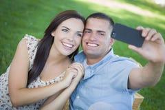 Couples de métis d'amusement prenant l'autoportrait en parc Photos libres de droits