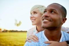 Couples de métis de millénaire dans un domaine d'herbe embrassant pour un instant d'offre d'amusement Photographie stock