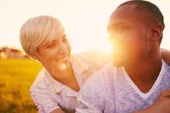 Couples de métis de millénaire dans un domaine d'herbe embrassant pour un instant d'offre d'amusement Photo libre de droits
