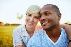 Couples de métis de millénaire dans un domaine d'herbe embrassant pour un instant d'offre d'amusement Image stock