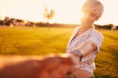 Couples de métis de millénaire dans un domaine d'herbe marchant et tenant des mains dans des vacances d'été Photos libres de droits