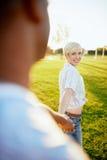 Couples de métis de millénaire dans un domaine d'herbe marchant et tenant des mains dans des vacances d'été Images stock