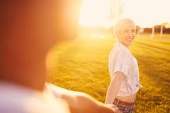 Couples de métis de millénaire dans un domaine d'herbe marchant et tenant des mains dans des vacances d'été Image libre de droits
