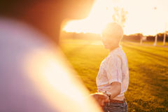 Couples de métis de millénaire dans un domaine d'herbe marchant et tenant des mains dans des vacances d'été Photographie stock libre de droits