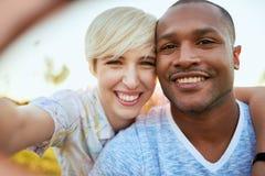 Couples de métis de millénaire dans un domaine d'herbe prenant un selfie avec un smartphone Image stock
