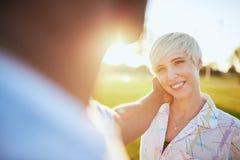 Couples de métis de millénaire dans un domaine d'herbe regardant l'ine yeux pendant des vacances d'été Image libre de droits