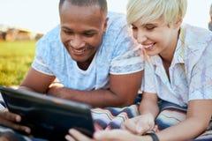Couples de métis de millénaire dans un domaine d'herbe regardant un comprimé numérique et lisant pour leur prochain papier d'écol Image stock