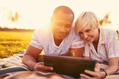 Couples de métis de millénaire dans un domaine d'herbe regardant un comprimé numérique et lisant pour leur prochain papier d'écol Images stock