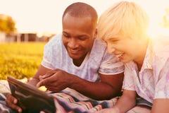 Couples de métis de millénaire dans un domaine d'herbe regardant un comprimé numérique et lisant pour leur prochain papier d'écol Photographie stock libre de droits
