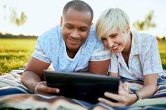 Couples de métis de millénaire dans un domaine d'herbe regardant un comprimé numérique et lisant pour leur prochain papier d'écol Photo libre de droits