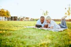 Couples de métis de millénaire dans un domaine d'herbe regardant un comprimé numérique et lisant pour leur prochain papier d'écol Photographie stock