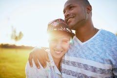Couples de métis des millennials dans un domaine d'herbe caressant et montrant l'affection ensemble Photos libres de droits