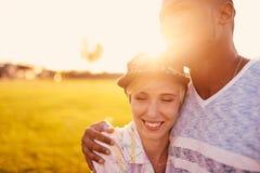 Couples de métis des millennials dans un domaine d'herbe caressant et montrant l'affection ensemble Images stock