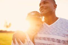 Couples de métis des millennials dans un domaine d'herbe caressant et montrant l'affection ensemble Photos stock