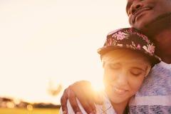 Couples de métis des millennials dans un domaine d'herbe caressant et montrant l'affection ensemble Image stock