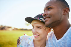Couples de métis des millennials dans un domaine d'herbe caressant et montrant l'affection ensemble Images libres de droits