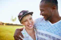 Couples de métis des millennials dans un domaine d'herbe caressant et montrant l'affection ensemble Photographie stock