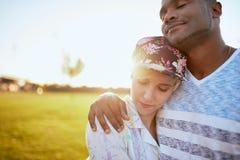 Couples de métis des millennials dans un domaine d'herbe caressant et montrant l'affection ensemble Photo libre de droits