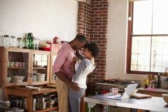 Couples de métis embrassant dans la cuisine Photo stock