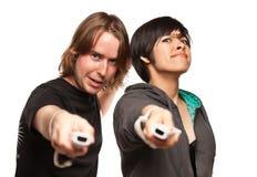 Couples de métis jouant des distants de jeu vidéo sur le blanc Images libres de droits
